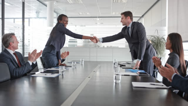 Caucasian businessman and African-American businesswoman signing a contract and shaking hands in front of colleagues in the conference room