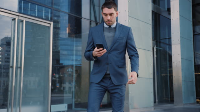 caucasian businessman in a suit is using a smartphone on a street in downtown. other office people walk past. he's confident and looks successful. he's browsing the web on his device. - pedone ruolo dell'uomo video stock e b–roll