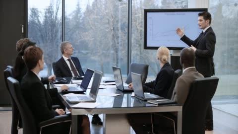 vídeos de stock e filmes b-roll de caucasian businessman leading a presentation in the meeting room - fato