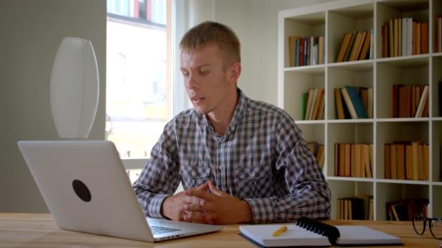 caucasian businessman talking in videochat being serious and attentive using laptop on bookshelves background. - surowy obraz filmowy filmów i materiałów b-roll
