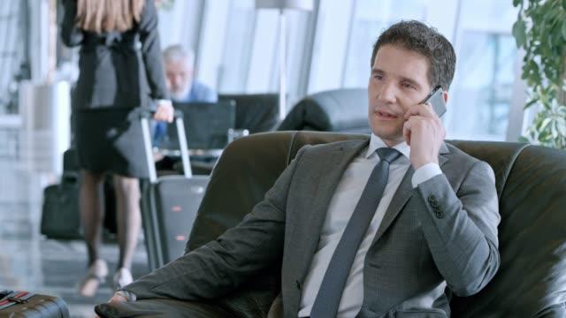 stockvideo's en b-roll-footage met ds kaukasische zakenman praten aan de telefoon in de business lounge op de luchthaven - vliegveld vertrekhal