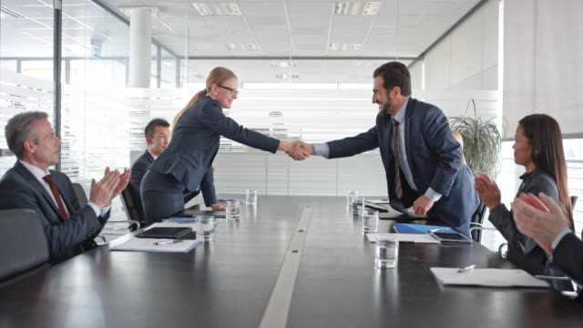 Caucasian businesswoman and businessman signing a contract and shaking hands and their two teams applaud in the conference room video