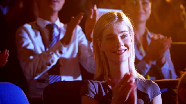 kaukasische geschäftsfrau applaudiert im business-seminar im auditorium 4k - zuschauerraum stock-videos und b-roll-filmmaterial