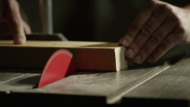 kaukasischer schreiner nutzt eine tischkreissäge, schnitt durch ein holzbrett - sägemehl stock-videos und b-roll-filmmaterial