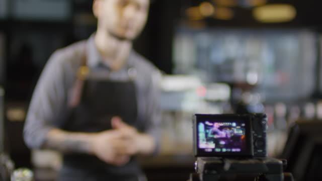 kaukasischer coffee shop manager giving interview auf kamera - hinter stock-videos und b-roll-filmmaterial