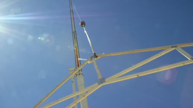 A Caucasian Construction Worker Attaches a Framed Wooden Roof Truss to a Hydraulic Crane that Then Lifts It into a Clear, Sunny Sky