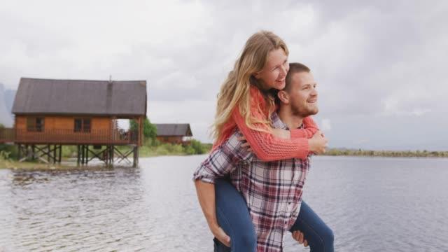 kaukasiska par har en bra tid på en resa till bergen, leende, mannen som håller kvinnan - människorygg bildbanksvideor och videomaterial från bakom kulisserna