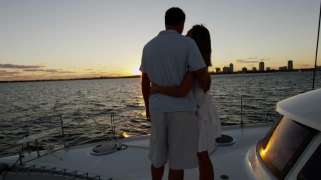 vídeos y material grabado en eventos de stock de beso pareja caucásica al atardecer en barco del océano - planificación financiera