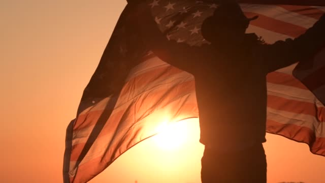 caucasian cowboy with american flag in slow motion - cowboy video stock e b–roll