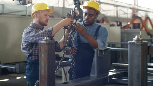 vídeos de stock e filmes b-roll de caucasian crane operator instructing black trainee - remote work