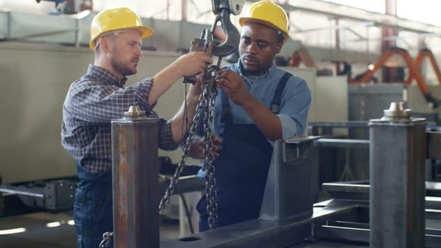 vídeos y material grabado en eventos de stock de operador de grúa caucásico instruyendo a aprendiz negro - pesado