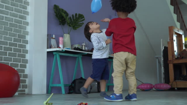 Caucasian ethnicity little boy and African-American Ethnicity little boy playing balloon together