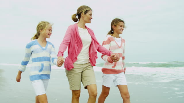 Caucasian Family Casual Clothing Enjoying Fall Beach Walking Caucasian mother daughters dressed casual clothes barefoot having fun walking sandy beach together Fall break shot on RED EPIC shallow stock videos & royalty-free footage