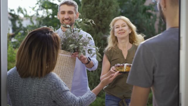 caucasian family giving presents to their new neighbors. friendly couple greeting newcomers - vicino video stock e b–roll