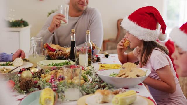 famiglia caucasica in cappelli di babbo natale che si gode il pranzo insieme mentre è seduta sul tavolo da pranzo a casa - pranzo di natale video stock e b–roll