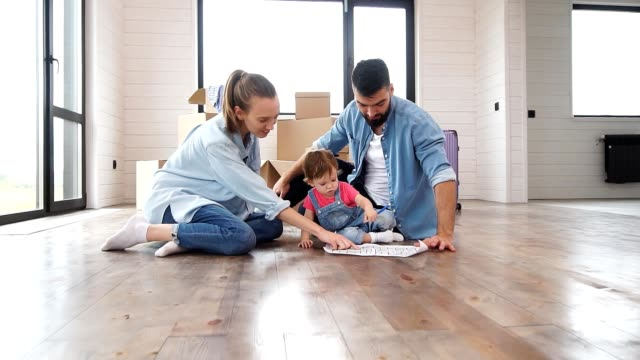 Caucasian family of three sit on floor in new house and look at house plan