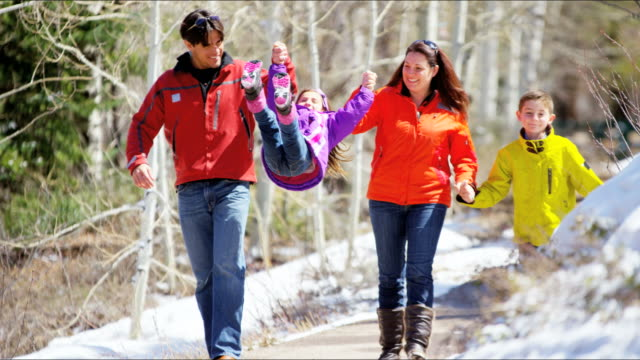 Caucasian family outdoors walking together winter mountains vacation video