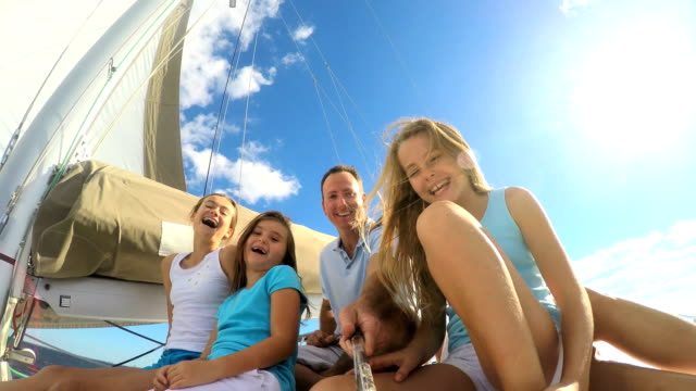 caucasian family smiling for video selfie on yacht - financial planning stock videos & royalty-free footage