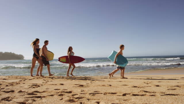 Caucasian family walking down the beach video