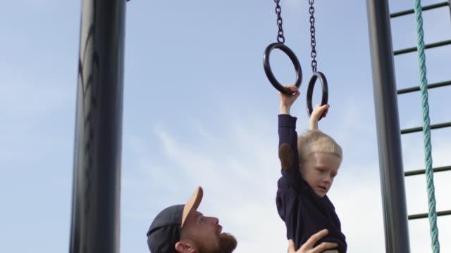 kaukasiska far lyfta son till flygande ringar på utomhus gym - gym skratt bildbanksvideor och videomaterial från bakom kulisserna