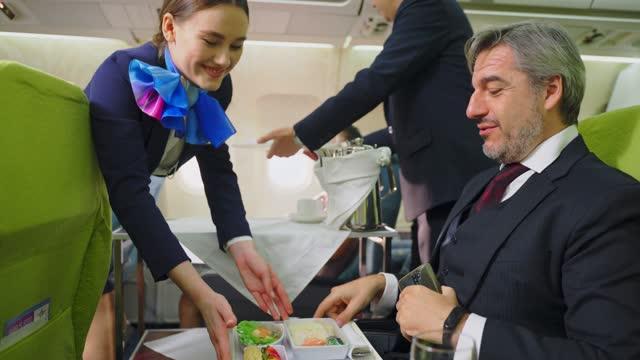 vídeos y material grabado en eventos de stock de una azafata de mujer y asiático que camina en pasillo para servir comida y servicio a todos los pasajeros en el camino. trabajo de la tripulación de cabina y servicio de ocupación a bordo en el concepto de avión. - snack aisle
