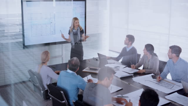 caucasian female architect giving a presentation of the plan details to her colleagues sitting in the conference room - leanincollection stock videos & royalty-free footage