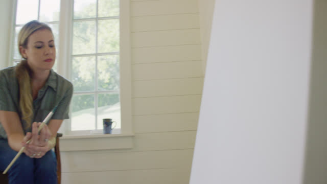 vidéos et rushes de une artiste féminine caucasienne dans sa quarantaine contemple une grande toile blanche tout en s'asseyant dans une chaise avec une tasse de café et plongeant un pinceau dans la peinture dans son studio d'art intérieur - toile à peindre