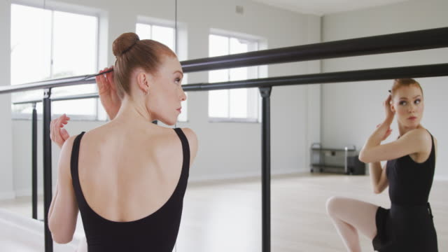 Caucasian female ballet dancer preparing for dance class in a bright studio
