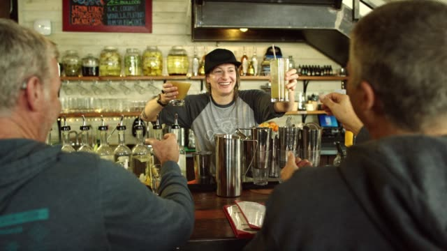 a caucasian female bartender in her thirties smiles at hands two caucasian men their cocktails while working at a bar - bartender stock videos and b-roll footage