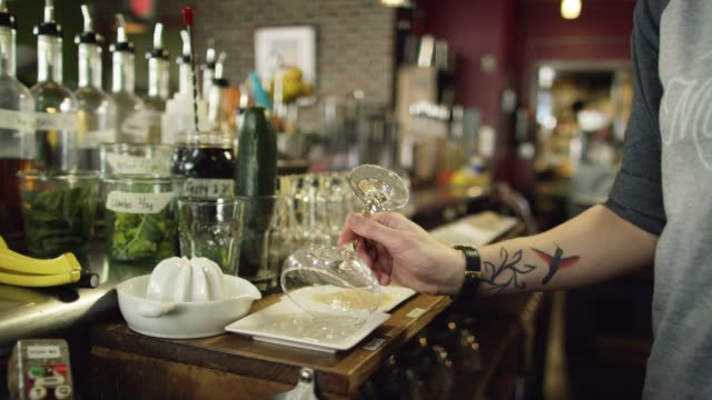 A Caucasian Female Bartender with Tattoos Dips a Martini Glass in Several Different Powders to Garnish the Rim Before Placing It on the Counter While Preparing Cocktails at a Bar A Caucasian Female Bartender with Tattoos Dips a Martini Glass in Several Different Powders to Garnish the Rim Before Placing It on the Counter While Preparing Cocktails at a Bar garnish stock videos & royalty-free footage