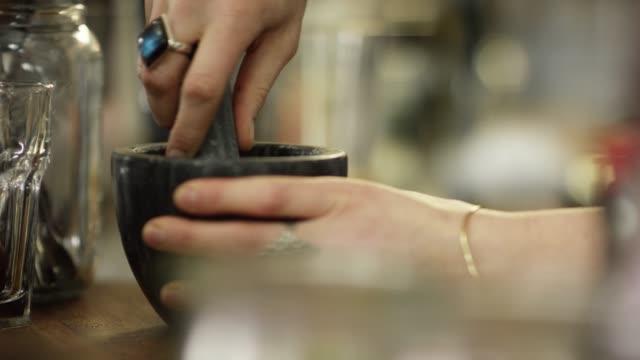 vidéos et rushes de un barman féminin caucasien avec des tatouages utilise un mortier et un pilon pour broyer des herbes et puis les ajoute à un cocktail qu'elle se prépare à un bar - plante aromatique