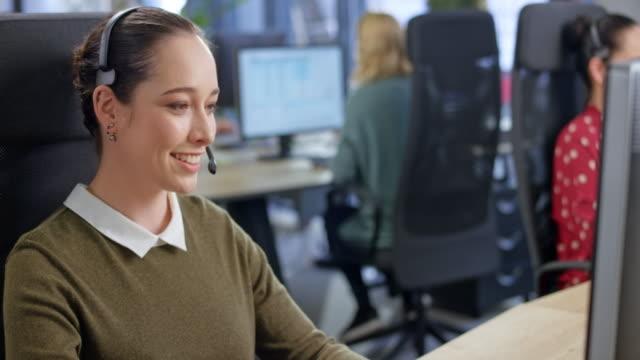 vidéos et rushes de agent féminin caucasien de centre d'appel parlant avec un client - relation client
