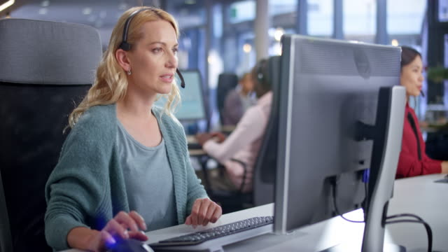 DS Caucasian female call centre agent providing customer service at her modern working station