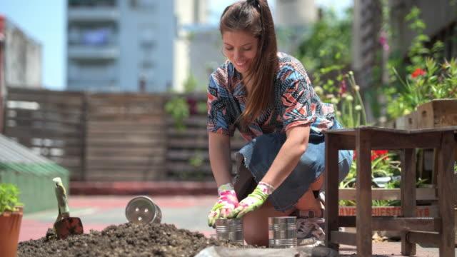 caucasian female gardener filling can with soil for planting - gardening video stock e b–roll
