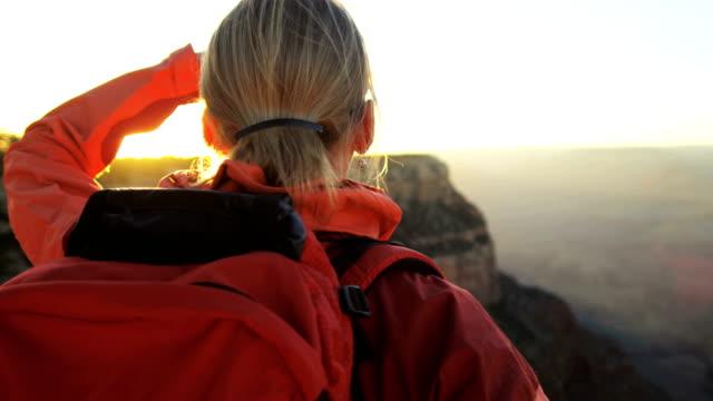 kaukasische weibliche wanderer anzeigen grand canyon bei sonnenuntergang - grand canyon stock-videos und b-roll-filmmaterial