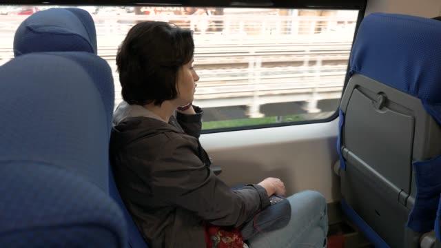 vídeos de stock, filmes e b-roll de mulher caucasiana de meia idade que fala na carruagem de assento do telefone do trem movente - mobile