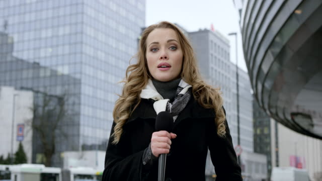 Caucasian female news reporter reporting from the business district Wide locked down shot of a Caucasian female news reporter reporting live from the business district. Shot in Slovenia. journalist stock videos & royalty-free footage