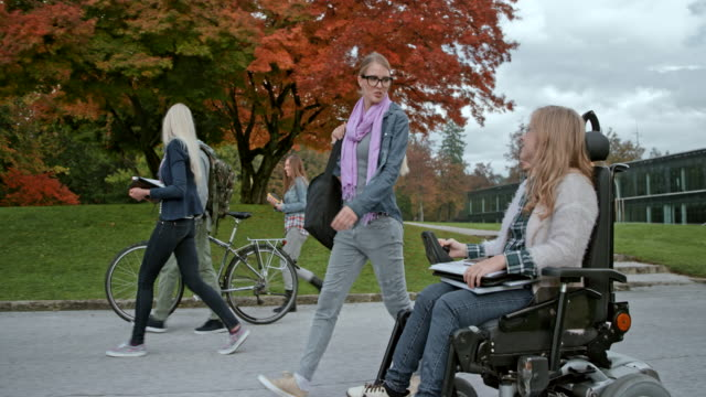 TS Caucasian female student in a wheelchair talking to her Caucasian female friend as they walk through the campus Wide tracking shot of a Caucasian female student in a wheelchair talking to her Caucasian female friend as they walk through the park on a cloudy day in fall. Shot in Slovenia. disability stock videos & royalty-free footage