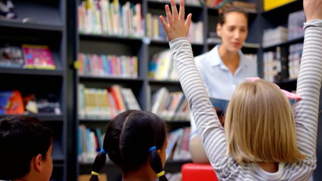 vídeos de stock e filmes b-roll de caucasian female teacher teaching schoolkids in the school library 4k - sabedoria