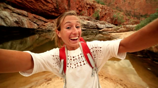 Caucasian female traveling takes a selfie portrait video