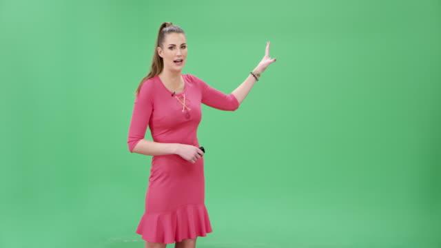 vídeos de stock e filmes b-roll de caucasian female weather presenter giving the weather forecast information - weatherman