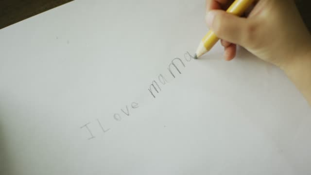 """a caucasian five year-old's hand writes """"i love mama"""" in pencil on a piece of paper - school supplies stock videos and b-roll footage"""