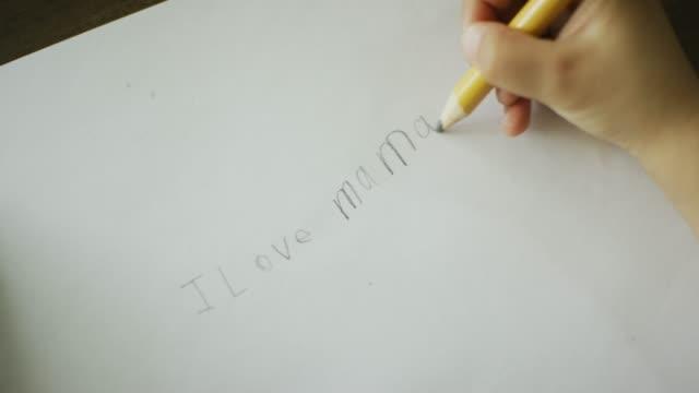 vidéos et rushes de une main de cinq ans caucasien écrit «i love mama» au crayon sur un morceau de papier - fournitures scolaires
