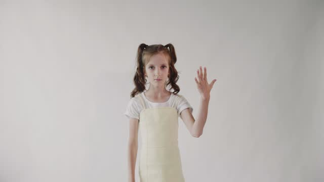 Caucasian girl counts to five on her fingers. Counting on the fingers. Isolated. White background.