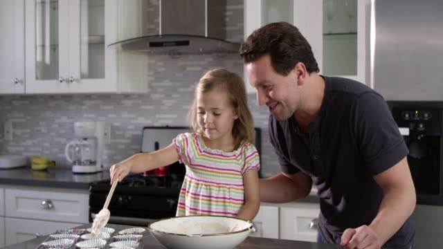 Caucasian girl spooning out cake mix mix for baking with her dad, shot on R3D video