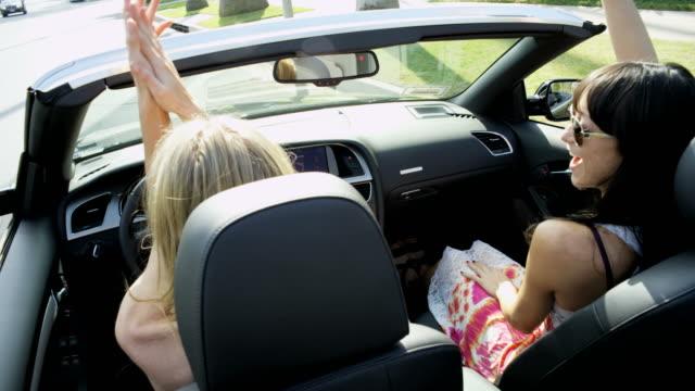 Caucasian girls enjoying glamorous lifestyle driving luxury car