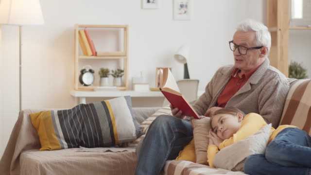 Caucasian Granddad Reading Aloud Book and Girl Listening Tilting full shot of elderly Caucasian grandfather with grey hair in glasses and cardigan sitting on couch and reading aloud book, and young granddaughter lying on pillows and listening granddaughter stock videos & royalty-free footage