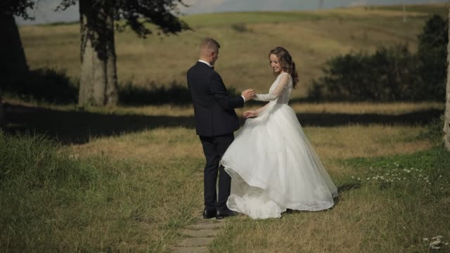 caucasian groom with bride in the park. wedding couple. happy family. newlyweds - figura femminile video stock e b–roll