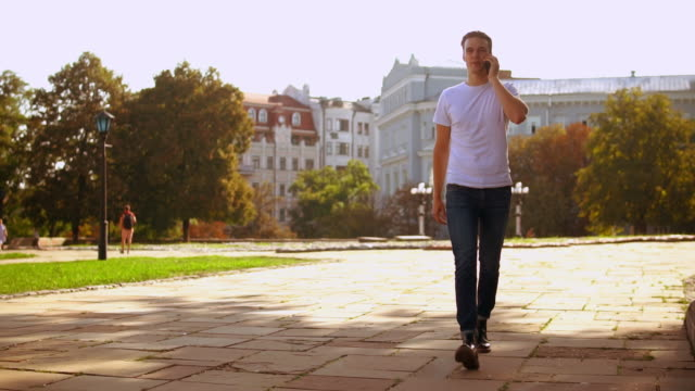 caucasian guy has phone conversation by mobile - maglietta bianca video stock e b–roll