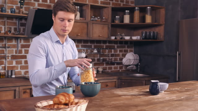 Caucasian guy sitting at the table with food in flat. video